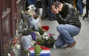 A man pays his respect outside the Le Carillon restaurant the morning after a series of deadly attacks in Paris , November 14, 2015. REUTERS/Christian Hartman TPX IMAGES OF THE DAY TPX IMAGES OF THE DAY