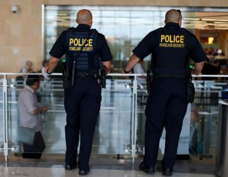 Homeland Security personnel keep watch as travelers depart at Lindbergh Field airport in San Diego