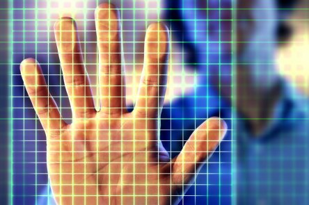 Man holding up hand to electronic grid, close-up (Composite)